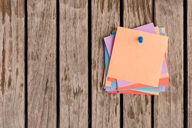 Tas de notes autocollantes attaché avec une punaise bleue sur une table en bois