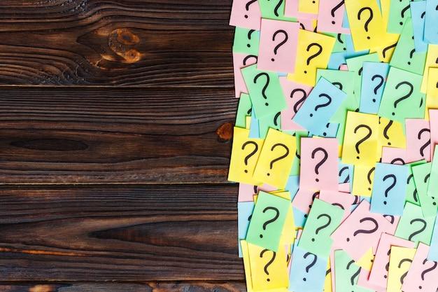 Tas de notes de papier colorées avec des points d'interrogation. vue de dessus espace de copie
