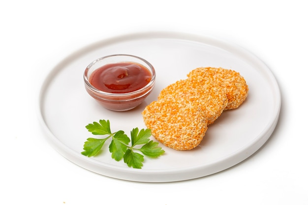 Un tas de nuggets de poulet cuits dans une assiette avec sauce tomate, isolé sur fond blanc