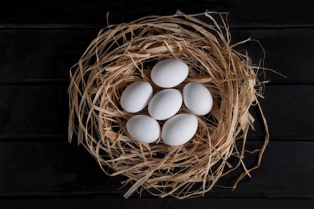 Tas d'oeufs frais crus dans le nid d'oiseau sur une surface noire. photo de haute qualité