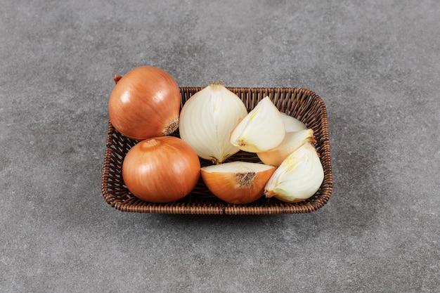Tas d'oignons mûrs entiers ou tranchés dans le panier