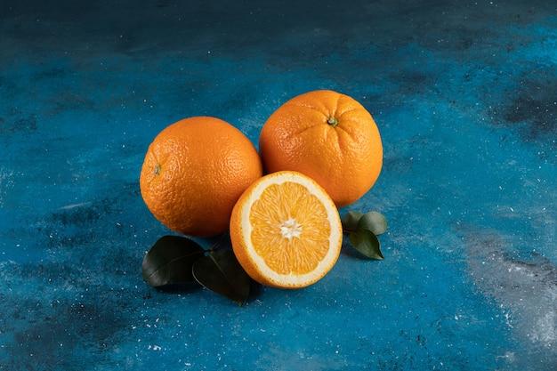 Un tas d'orange fraîche, sur la surface bleue