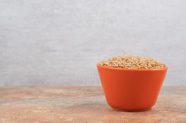 Tas d'orge dans un bol rouge sur fond orange