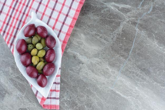Tas de palmiers et d'olives sur plaque blanche.