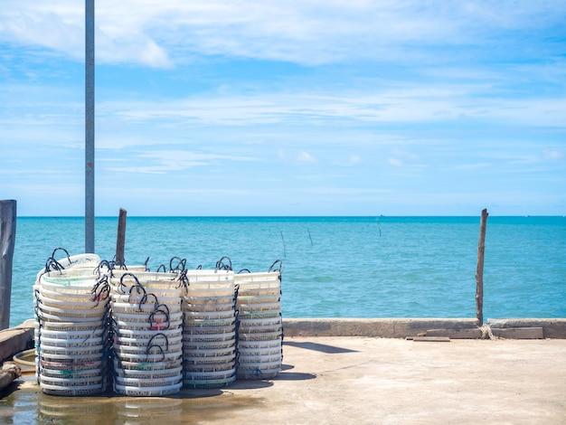 Des tas de paniers de pêcheurs blancs vides à sécher au soleil sur le quai.