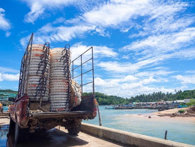 Des tas de paniers de pêcheurs blancs vides à sécher au soleil sur un vieux camion au quai.