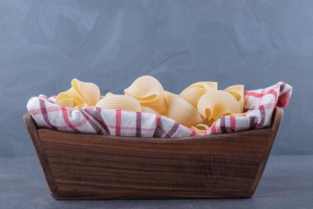 Tas de pâtes coquillages crus dans une boîte en bois.
