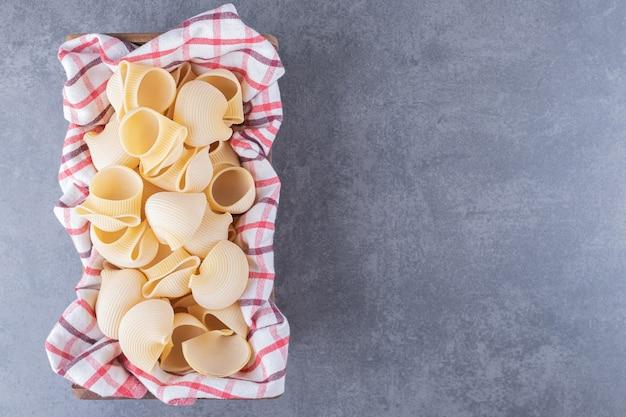 Tas de pâtes coquillages crus dans un panier avec nappe.