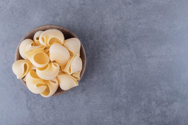 Tas de pâtes en coquille crue dans un bol en bois.