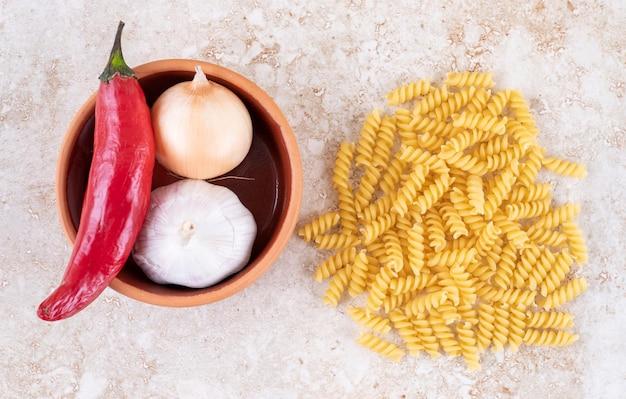 Tas de pâtes à côté d'un petit bol de poivron, oignon et ail sur une surface en marbre