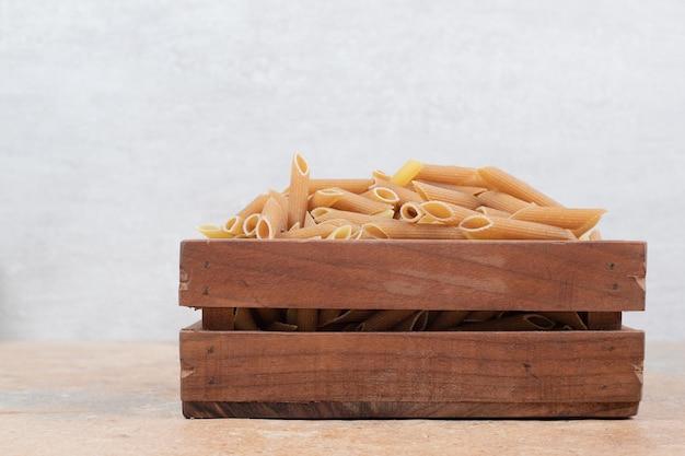 Tas de pâtes crues dans un panier en bois sur un espace en marbre.