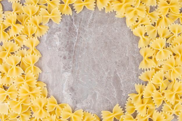 Un tas de pâtes farfalle, sur le marbre.