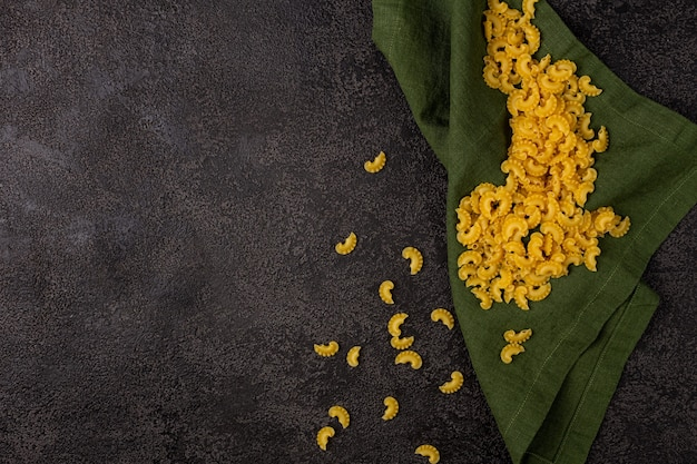 Un tas de pâtes jaunes crues isolées sur un fond structurel sombre avec un espace pour copier. vue de dessus de pâtes. pâtes sur une serviette en lin verte