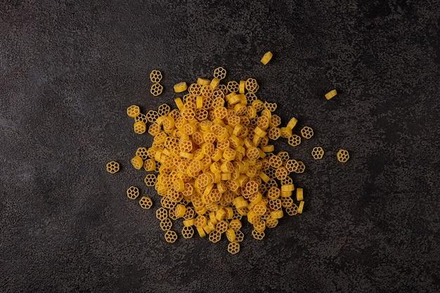 Un tas de pâtes jaunes crues, isolées sur un fond structurel sombre avec un espace pour copier. vue de dessus