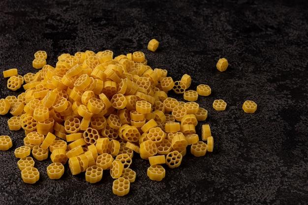 Un tas de pâtes jaunes crues, isolées sur un fond structurel sombre avec un espace pour copier.