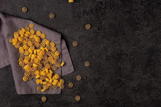 Un tas de pâtes jaunes crues sur une serviette en lin sur un fond structurel sombre avec un espace pour copier. vue de dessus