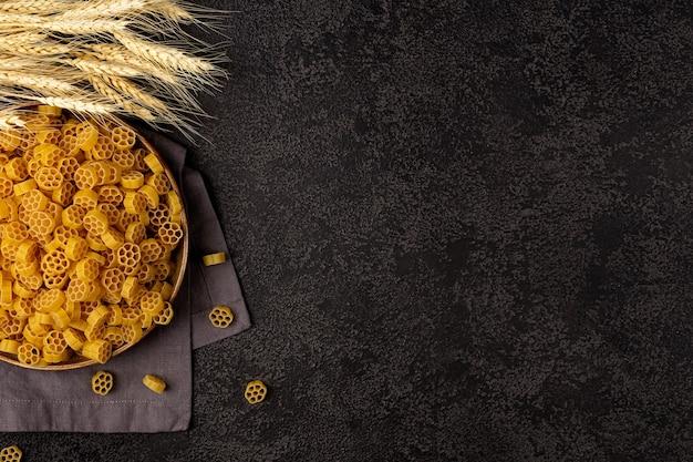 Un tas de pâtes jaunes crues sur une serviette en lin sur un fond structurel sombre avec un espace pour copier.