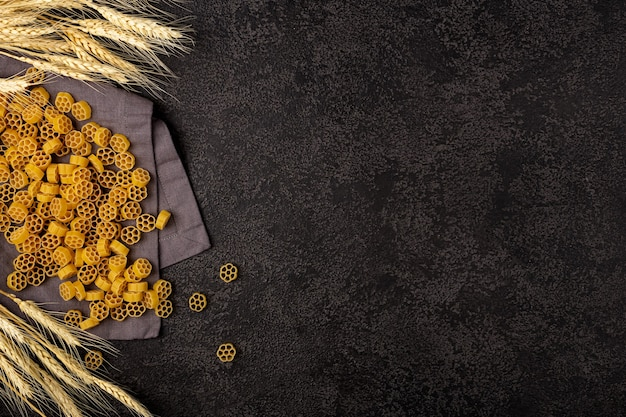 Un tas de pâtes jaunes crues sur une serviette en lin gris sur un fond structurel sombre avec un espace pour copier. épis de blé