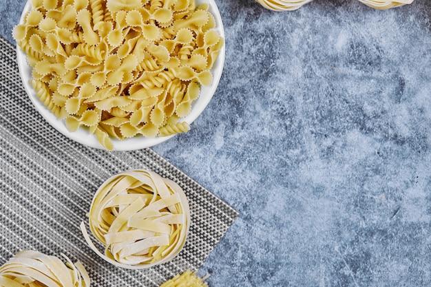 Un tas de pâtes non cuites sur du marbre.