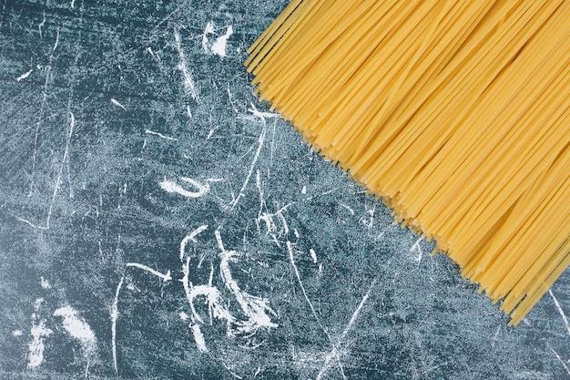 Tas de pâtes non préparées de spaghettis de grains entiers attachés avec une corde sur fond de marbre