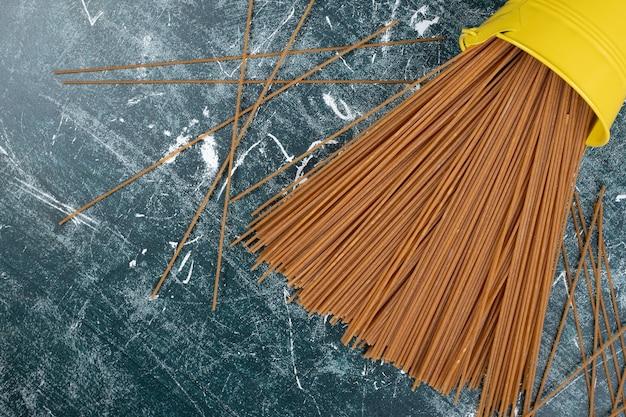 Tas de pâtes non préparées de spaghettis de grains entiers sur fond de marbre