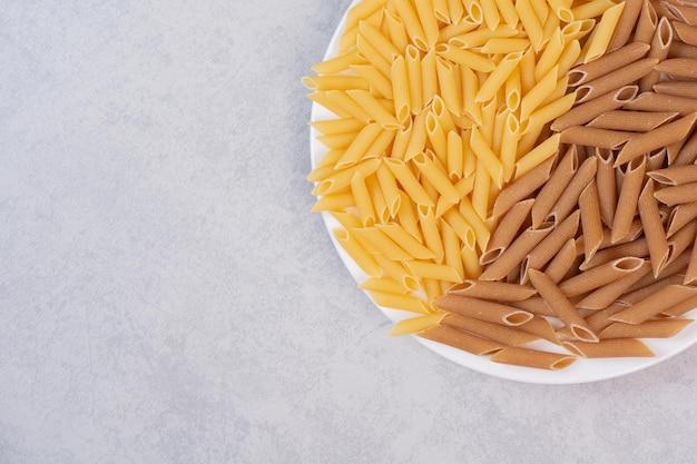 Tas de pâtes penne brunes et jaunes sur plaque blanche.