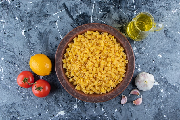 Tas de pâtes rigate de pipette crues dans un bol avec des tomates rouges fraîches et de l'huile.