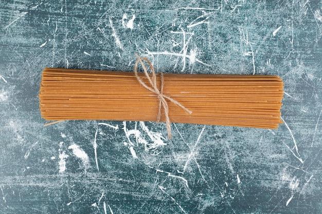 Tas de pâtes de spaghettis à grains entiers attachés avec une corde sur fond de marbre. photo de haute qualité