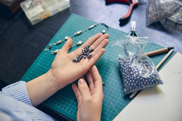 Un tas de perles chatoyantes à la main d'un bijoutier expérimenté