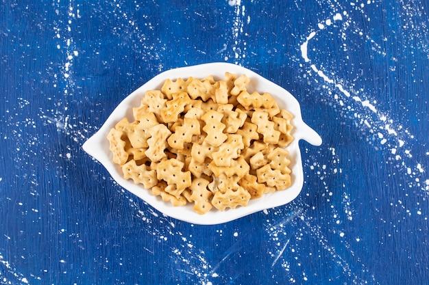 Tas de petits craquelins salés placés sur une assiette en forme de feuille