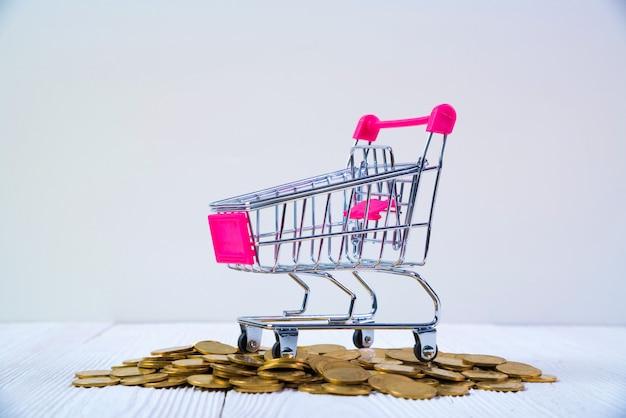 Tas de pièces de monnaie et caddie ou chariot de supermarché