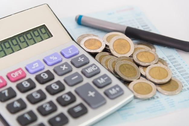 Des tas de pièces de monnaie et calculatrice avec stylo