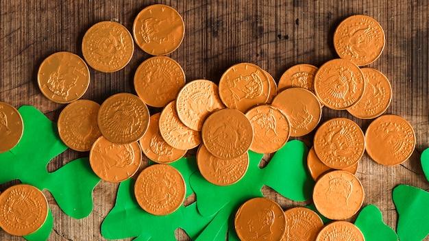 Tas de pièces de monnaie et de trèfles en papier sur une table en bois
