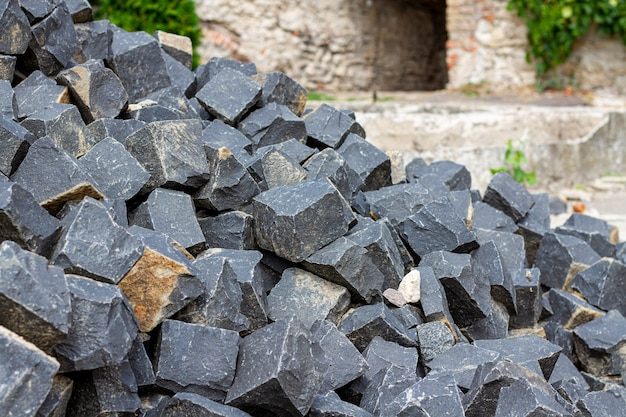 Un tas de pierres de matériaux de construction. pierres pour pavés et trottoirs en maçonnerie. construction de pavés de granit foncé.