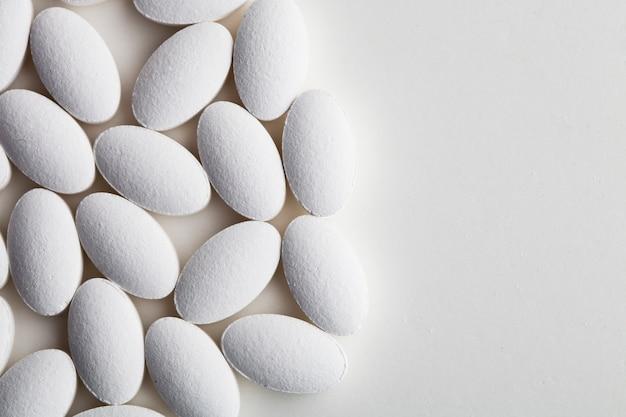 Tas de pilules blanches de drogue portant