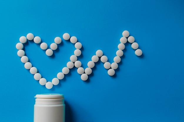 Tas de pilules sur bleu assortiment de pilules, de comprimés et de capsules de médicaments pharmaceutiques et bouteille sur bleu