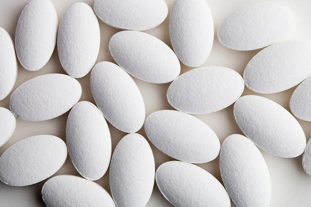 Tas de pilules de drogue blanche portant sur fond blanc.