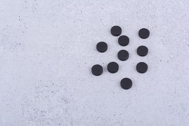 Tas de pilules noires sur fond de marbre. photo de haute qualité
