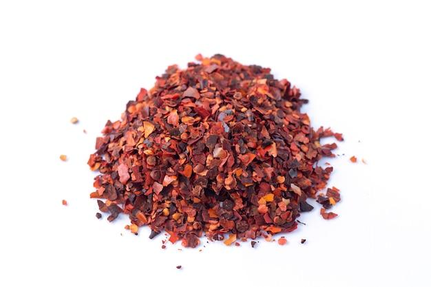 Tas de piment rouge broyé, flocons de piment de cayenne séchés isolés sur fond blanc