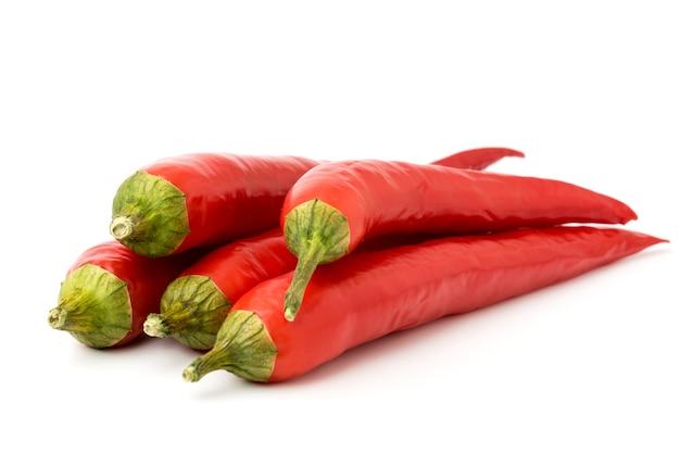 Tas de piments rouges chauds close-up sur blanc.