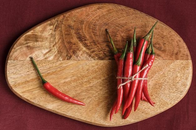 Un tas de piments rouges sur un support en bois sur fond noir. concept culinaire. épice chaude. fermer.