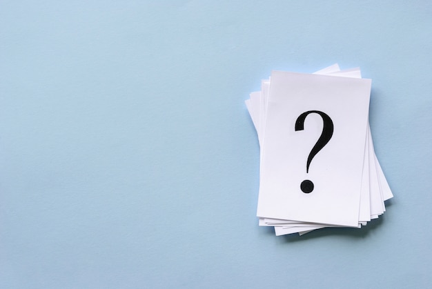 Tas de points d'interrogation empilés sur du papier blanc