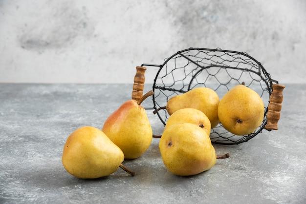 Tas de poires jaunes fraîches dans un seau en métal sur une surface en marbre.