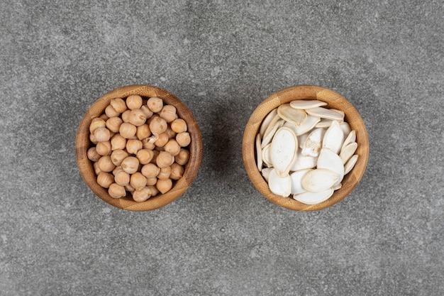 Tas de pois jaunes et de graines de citrouille dans des bols en bois.