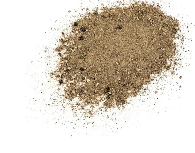 Tas de poivre noir moulu isolé sur blanc vue de dessus. l'épice ressemble à du sable dispersé à plat et vue de dessus