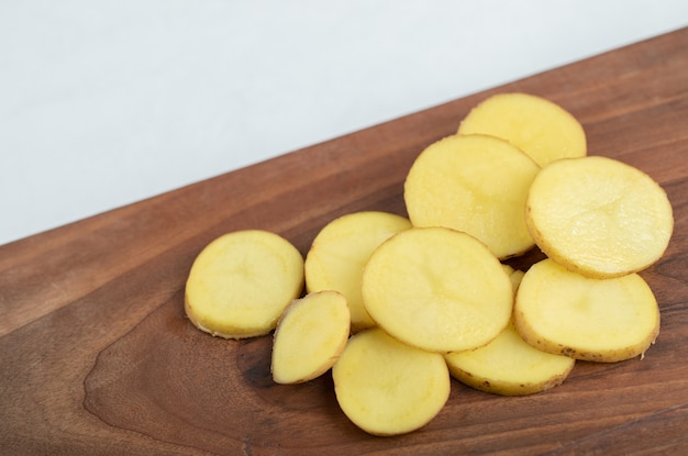 Tas de pommes de terre en tranches sur planche de bois.