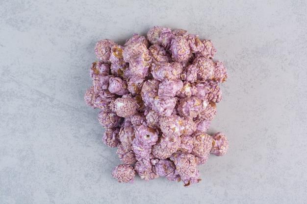 Tas de pop-corn sucré recouvert de bonbons violets sur marbre.