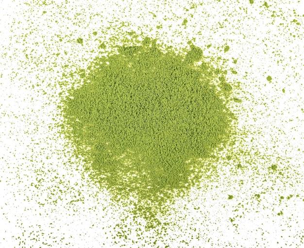 Tas de poudre de thé vert matcha sur fond blanc, vues de dessus