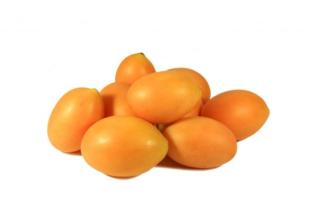 Tas de prune marian mûre vibrante orange jaune frais ou fruits ma-prang isolé sur fond blanc