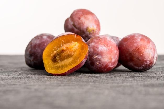 Tas de prunes fraîches entières avec une moitié équilibrée devant montrant la texture juteuse de la chair orange et de la pierre ou du pépin, angle faible avec fond.